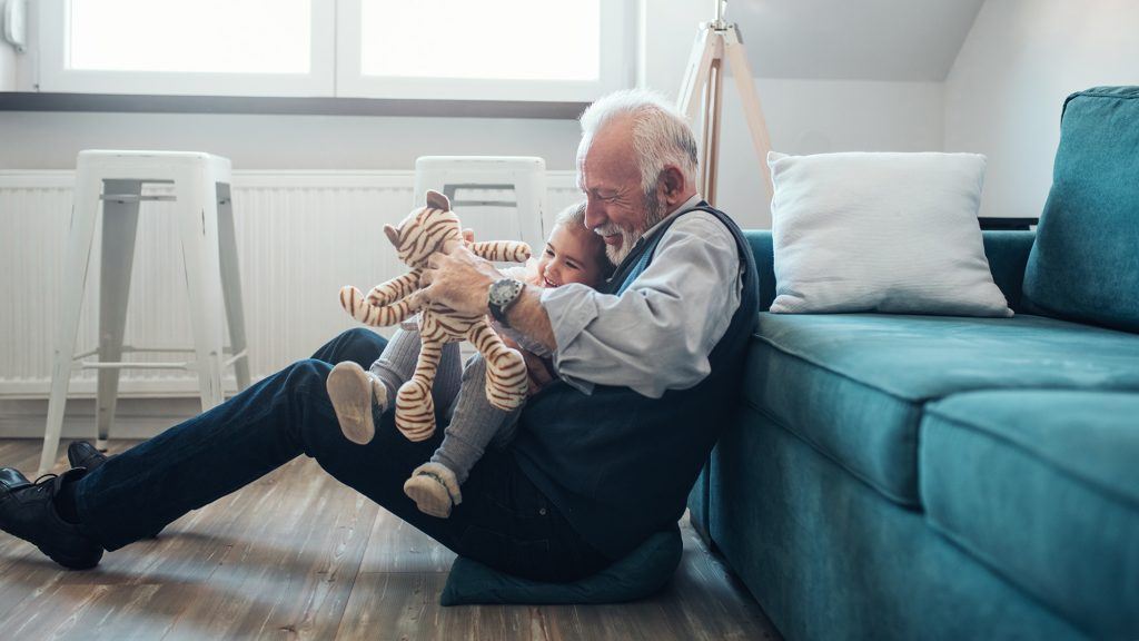 Mature man playing with granddaughter at home
