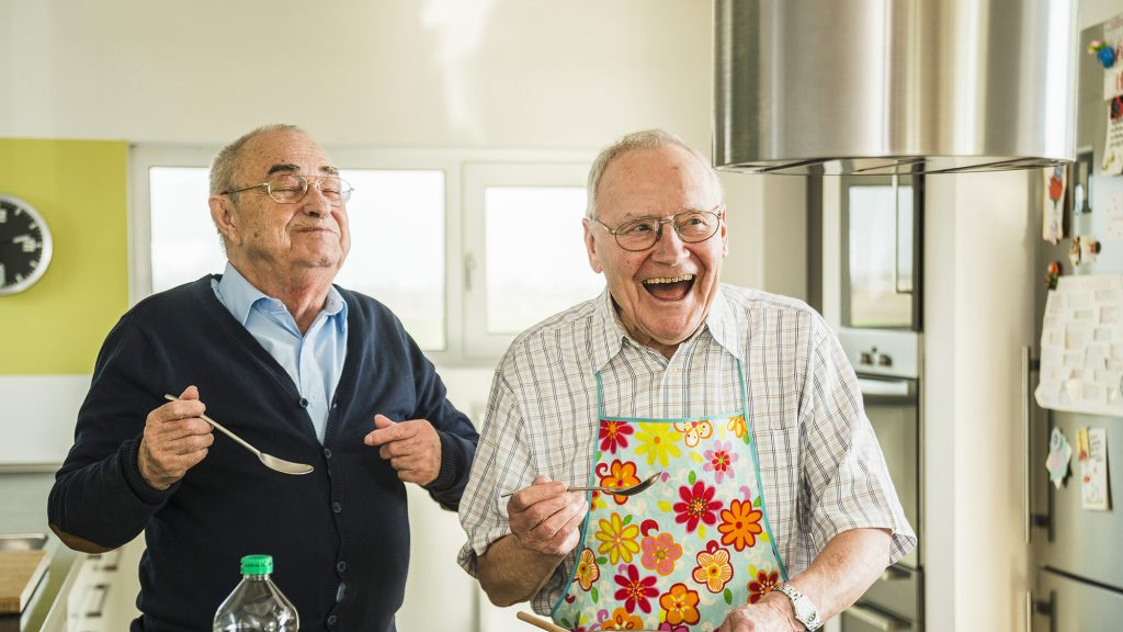 Two happy senior friends cooking in kitchen