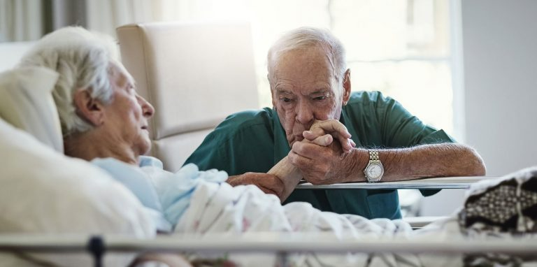 Senior man kissing hospitalised wifes hand